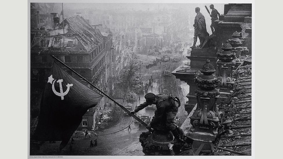 Yevgeny Khaldei manipulated his photo of Soviet soldiers raising the red flag over the Reichstag (1945) to hide the soldiers' looting (Credit: The David King Collection at Tate)