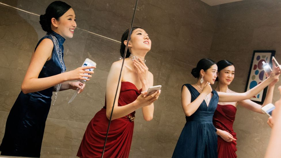 Young models in China take selfies during a fashion show (Credit: Getty Images)