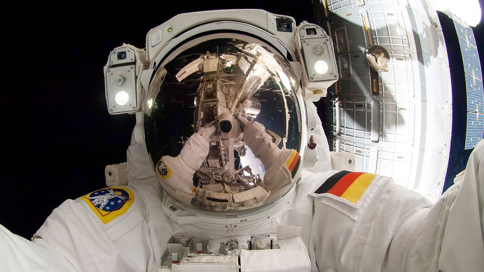 Astronaut with arms reflected in visor (Credit: Getty Images)