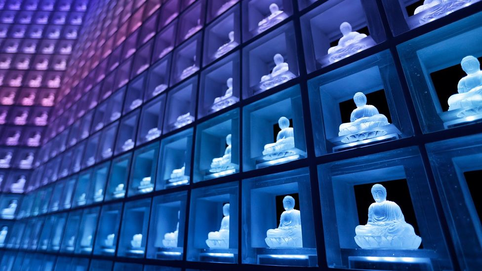 In facilities like this one in Japan, ashes are kept in urns behind glowing buddhas - allowing many people to be laid to rest in one room (Credit: Getty Images)