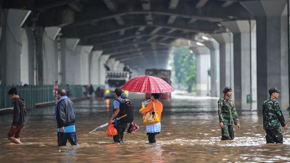 People stand on a flooded street in Jakarta, which struggles with subsidence (Credit: Alamy)