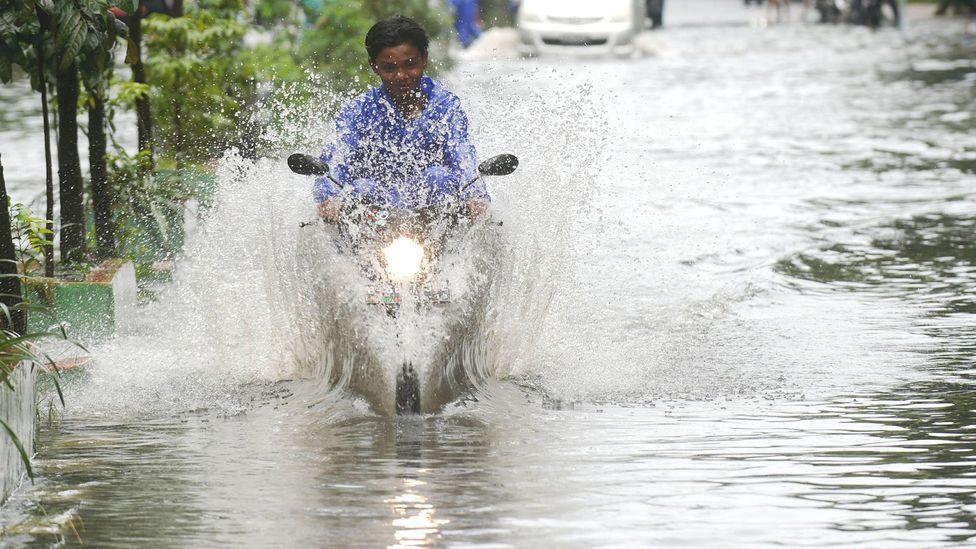 A man rides his motorcycle along a flooded street in Jakarta, a city facing the twin challenges of sea level rise and subsidence (Credit: Alamy)