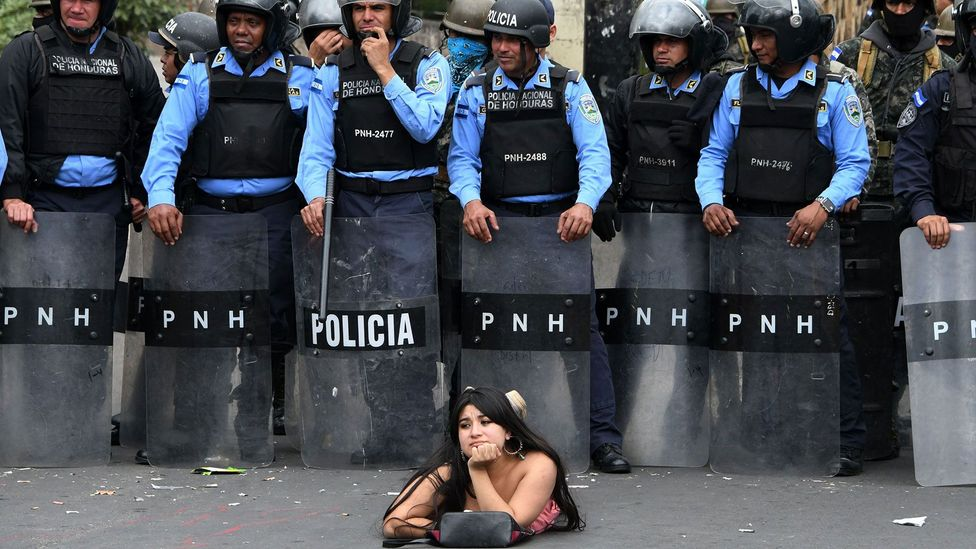 A protestor lies on the street in front of police officers during a demonstration against the contested re-election of President Hernandez in Honduras (Credit: Getty Images)