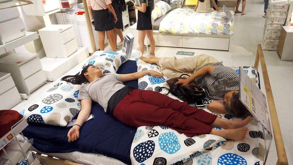People nap on a bed at an Ikea store to escape the heat outside in Hangzhou, China, in 2017 (Credit: Getty Images)
