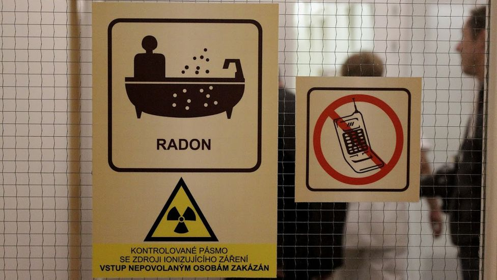 Stickers adorn entrance to an area where radon water therapy is carried out, warning of radioactive material (Credit: Matthew Vickery)