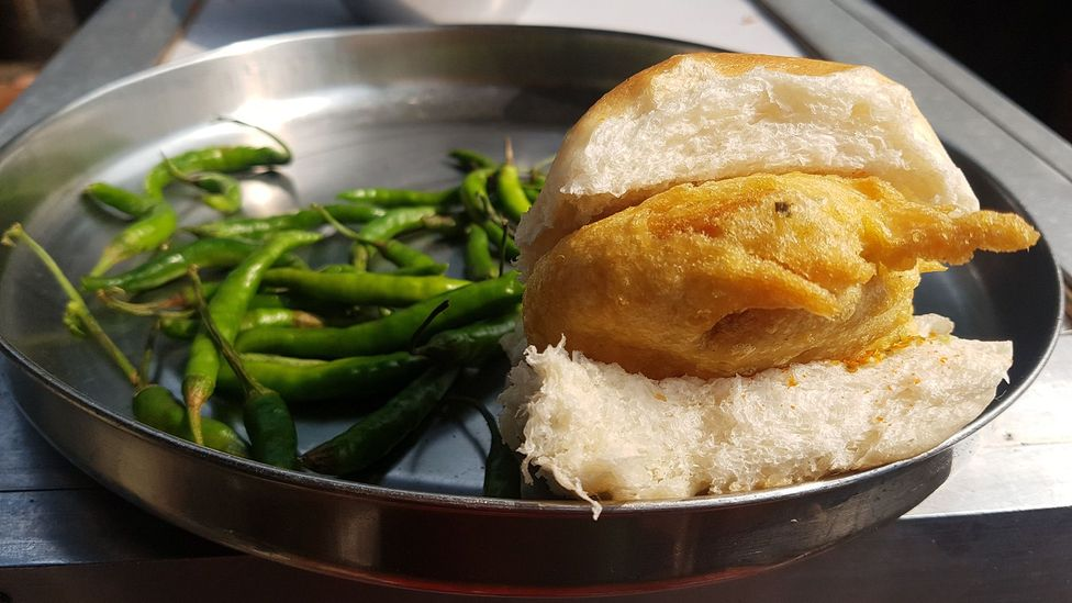Vada pav is a deep-fried potato patty served on a soft bread roll with spicy green chilli (Credit: Charukesi Ramadurai)