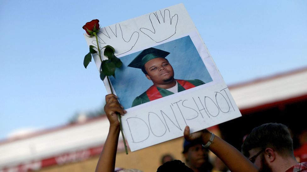 A demonstrator holds up a picture of 18-year-old Michael Brown, who was shot and killed by a police officer in Ferguson, Missouri in 2014 (Credit: Getty Images)