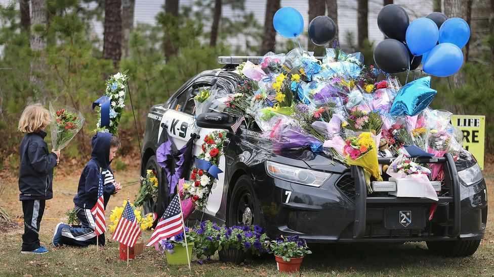 Boys leave flowers at the cruiser of Massachussetts police officer Sean Gannon, who was shot and killed in April 2018 while serving a warrant (Credit: Getty Images)