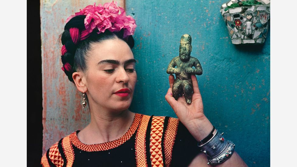 Frida Kahlo's iconic status owes much to her striking self-portraits, like this one, with an Olmec figurine, from 1939 (Credit: Nickolas Muray/Victoria and Albert Museum)