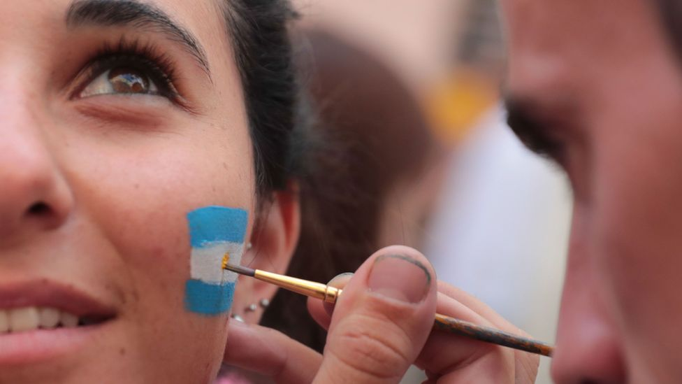 Woman with flag painted on cheek (Credit: Getty Images)