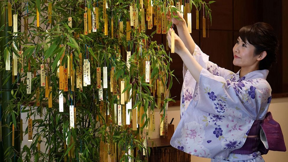 Japanese culture is heavily represented in emoji – here, a woman celebrates Tanabata, the annual star festival, with a decoration (which has its own emoji) (Credit: Getty Images)