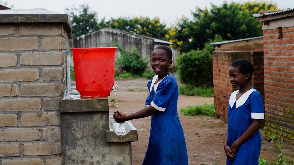 Girls wash their hands at their school's facilities in Malawi – one example of how people's behaviour can be changed to save lives (Credit: Getty Images)