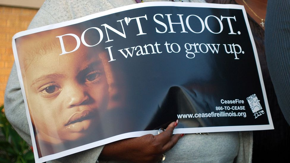 A woman holds a poster at an anti-violence rally on Chicago's South Side