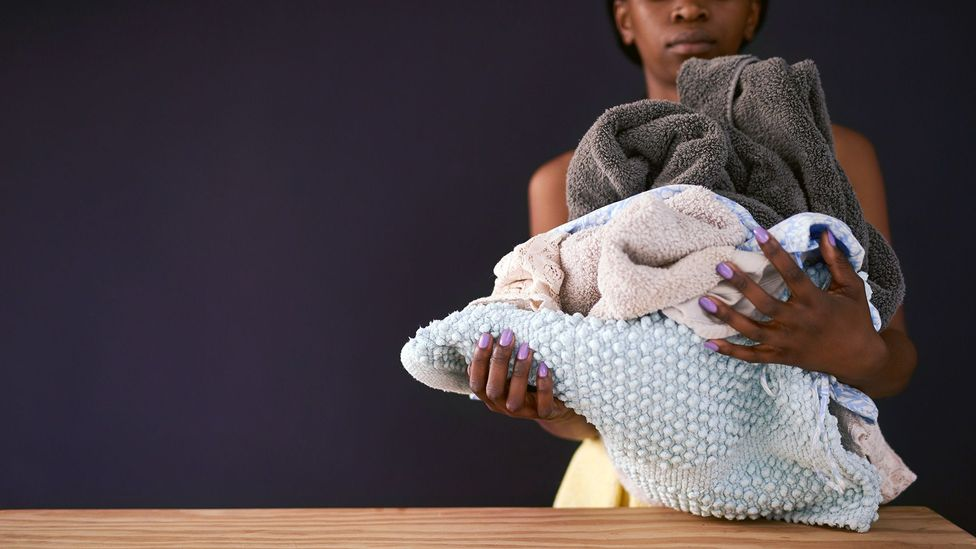 A woman is shown holding a pile of laundry (Credit: Getty Images)