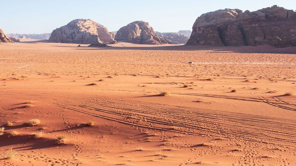 View of Wadi Rum, Jordan, with a vehicle in the distance