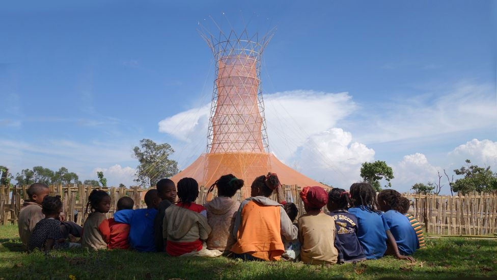Children in Dorze, Ethiopia, sit around the Warka Tower, which can collect drinking water from moisture from the air (Credit: Warka Water)