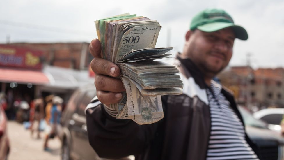 Venezuela's economy is in the midst of a crisis, and the country is filled with stacks of its devalued cash, as seen here on the border of Colombia (Credit: Getty Images)