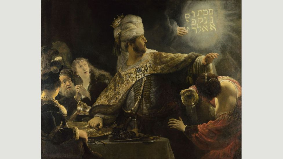 Rembrandt's Belshazzar's Feast shows a divine hand inscribing a warning to the king of Babylon after he blasphemously served wine in a looted sacred vessel (Credit: Wikimedia)