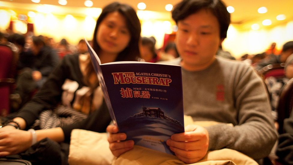 Audience members read the playbill ahead of a performance of Christie's The Mousetrap, at the Shanghai Lyceum Theatre (Credit: Getty)