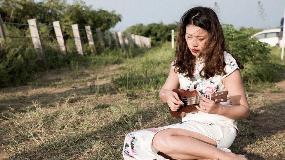 Chang performs songs that were played to soldiers in the past, moving from inside the tower to sit on the grass outside (Credit: Shao Po Chao)