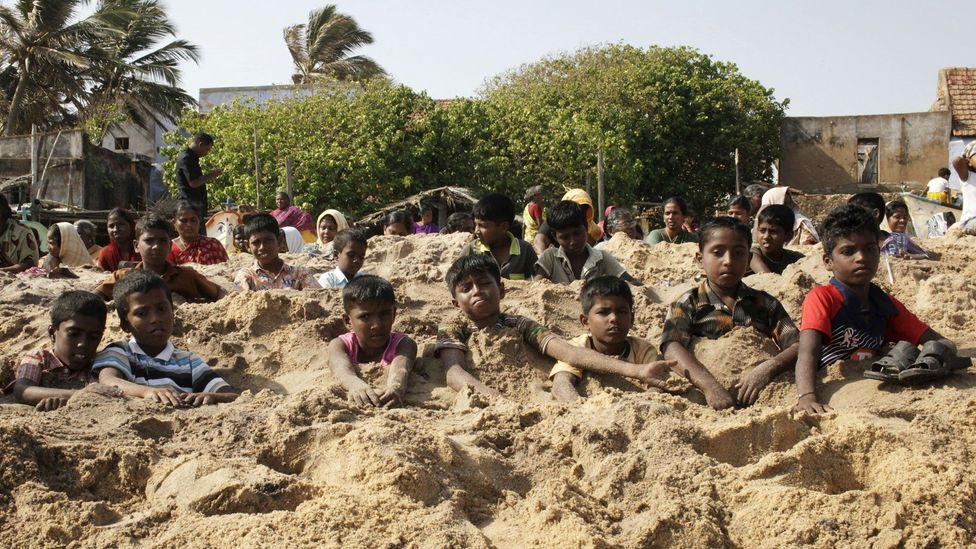 Activists from Tamil Nadu bury themselves to protest the loading of a uranium reactor. Yet the same sand holds thorium, a potentially safer nuclear power (Credit: Getty Images)