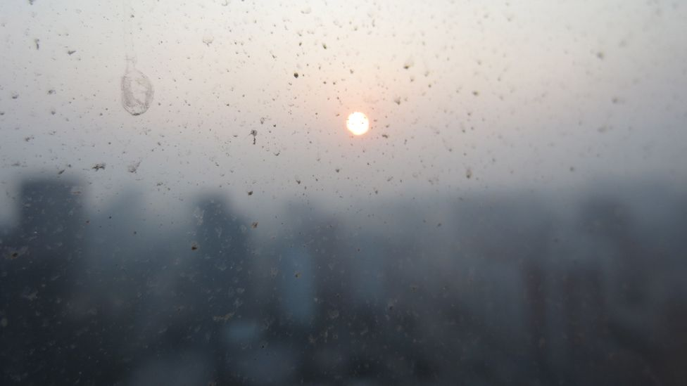 Pollution and smog make the sun hazy behind a dirty window in Beijing, China (Credit: Getty Images)