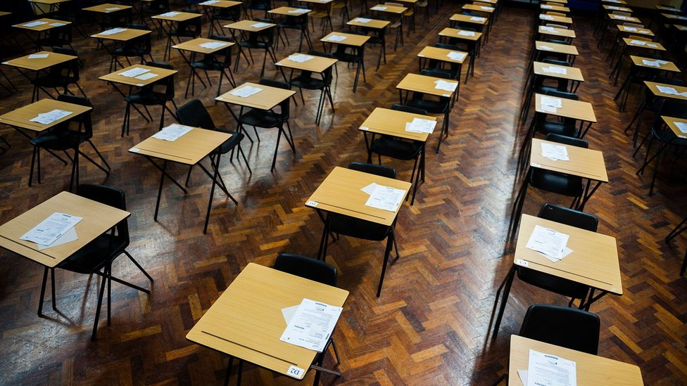 Rows of empty desks fill a Welsh school hall, ready for GCSE school pupils to sit their exams (Credit: Getty Images)
