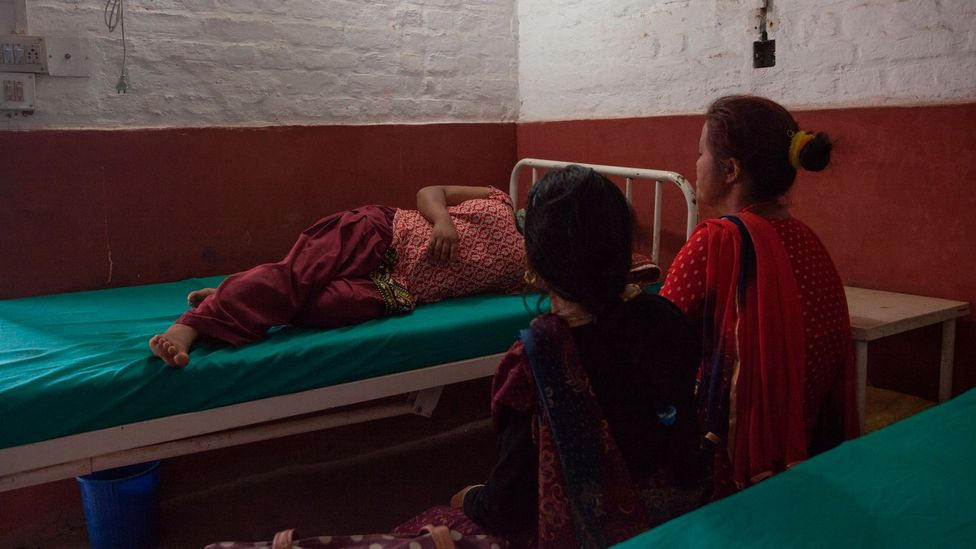 Maya, 34, waits in the examination room inside the one-stop crisis centre with her mother and neighbour (Credit: Bunu Dhungana)