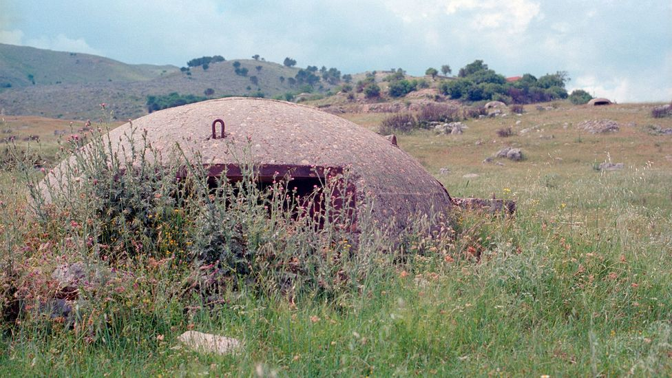 Many of the bunkers are now overgrown and left alone in the Albanian countryside (Credit: Stephen Dowling)