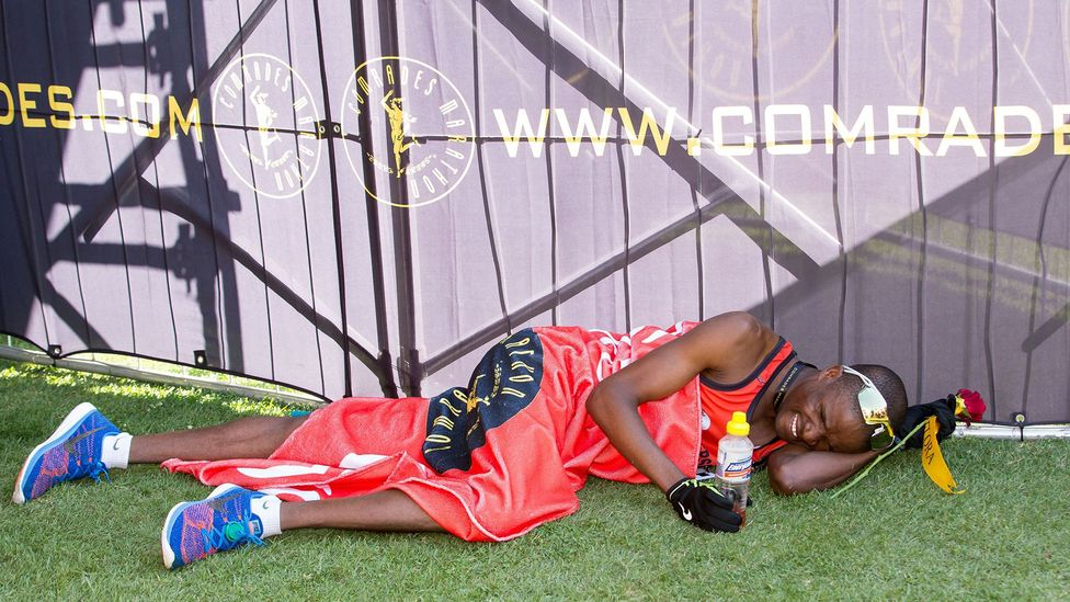 A runner lies on the ground after finishing South Africa's 89.2km Comrades Marathon, one of the most gruelling ultramarathons in the world (Credit: Getty)