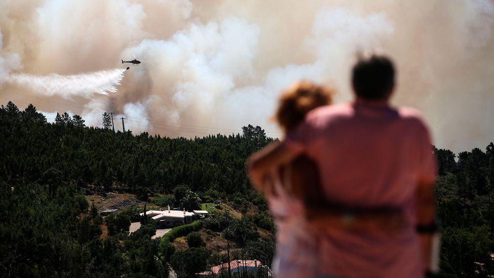 A helicopter drops water on a wildfire in Portugal's Algarve in August 2018. Experts say that pumping money into fire fighting might have diminishing returns (Credit: Getty)