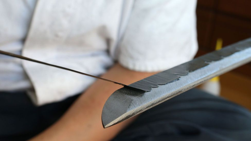 Before it enters the furnace, the swordsmith covers the blade with clay. This ensures the edge hardens more than the spine, which creates the sword's curve (Credit: Getty Images)