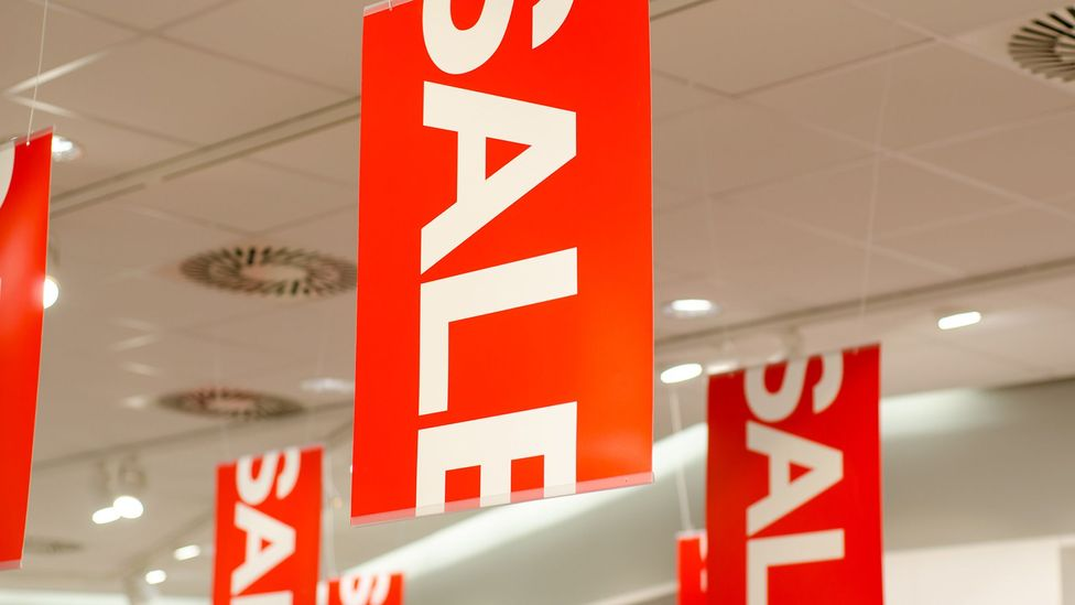 Sale signs hanging in a store (Credit: Getty)