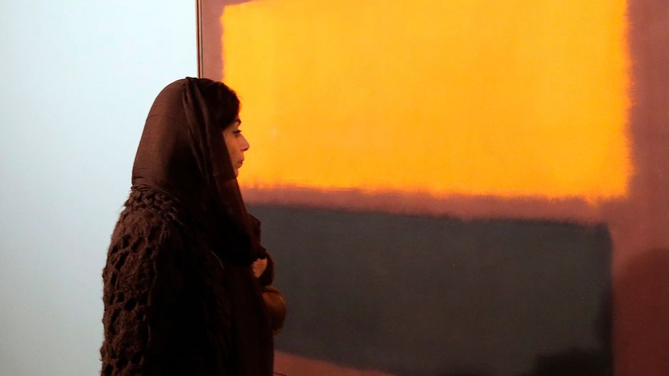 An Iranian woman looks at Sienna, Orange and Black on Dark Brown by Mark Rothko during an exhibition of modern art at TMOCA in 2015 (Credit: Getty Images)