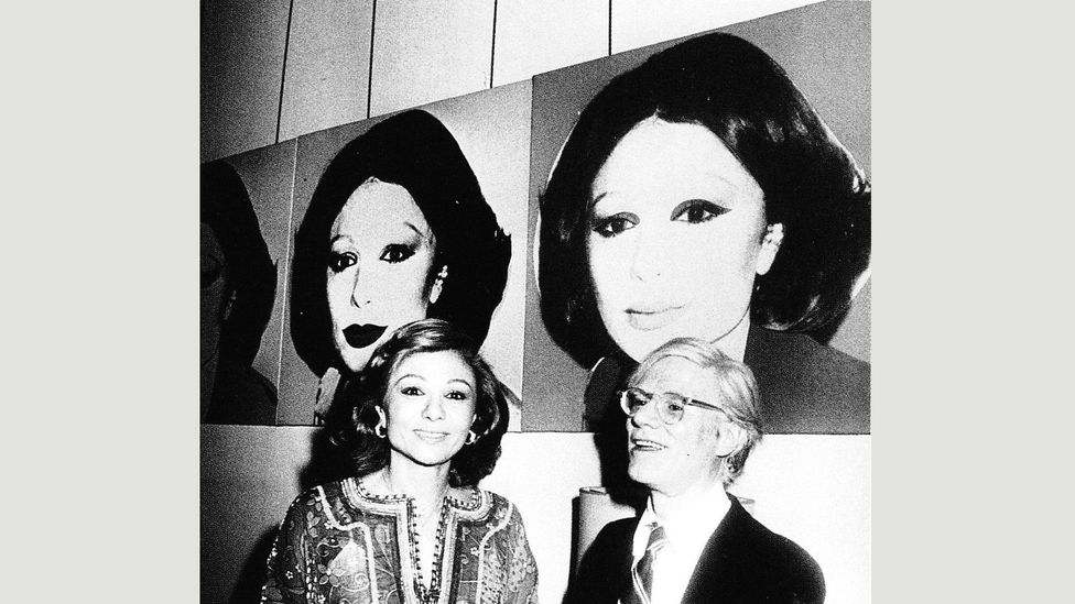Farah Pahlavi and Andy Warhol in front of his portrait of her at the Waldorf Astoria in New York on 13 July 1977 (Credit: Alamy)