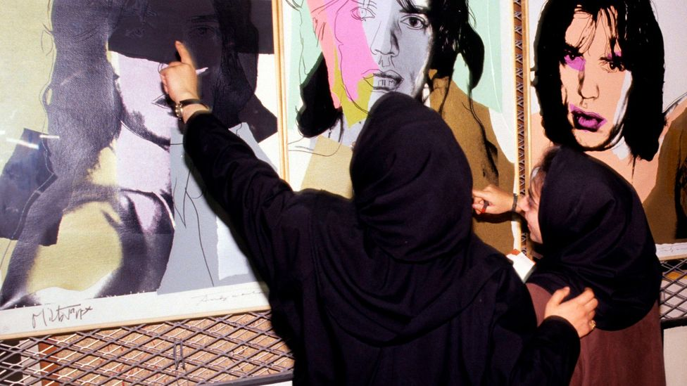 Two female staff at the Tehran Museum of Contemporary Art (TMOCA) examine portraits of Mick Jagger by Andy Warhol in the cellar of the museum in 1993 (Credit: Getty Images)