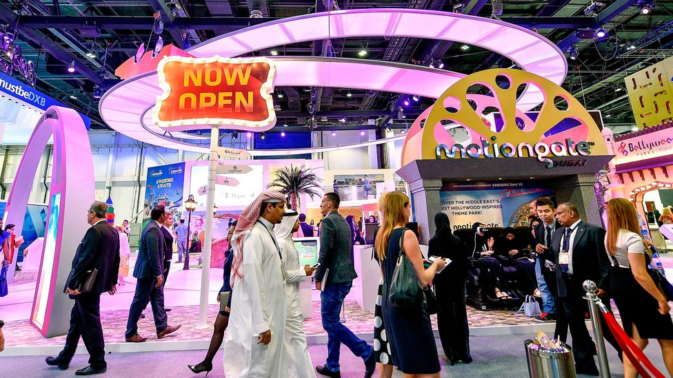 Visitors pass the Dubai Parks and Resorts stand during the Arabian Travel Market 2017 (Credit: Getty Images)