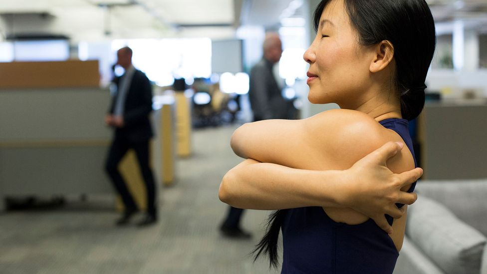 A fitness instructor teaches offices workers yoga techniques in Toronto (Credit: Getty Images)