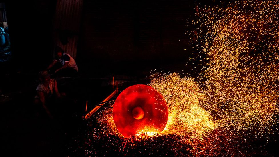 A worker heats a metal plate as they make traditional gong instruments in Indonesia (Credit: Getty Images)
