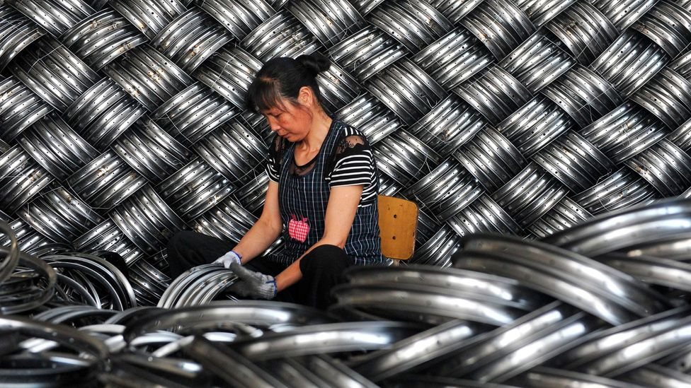 A worker in China checks wheel hubs ready to be exported (Credit: Getty Images)