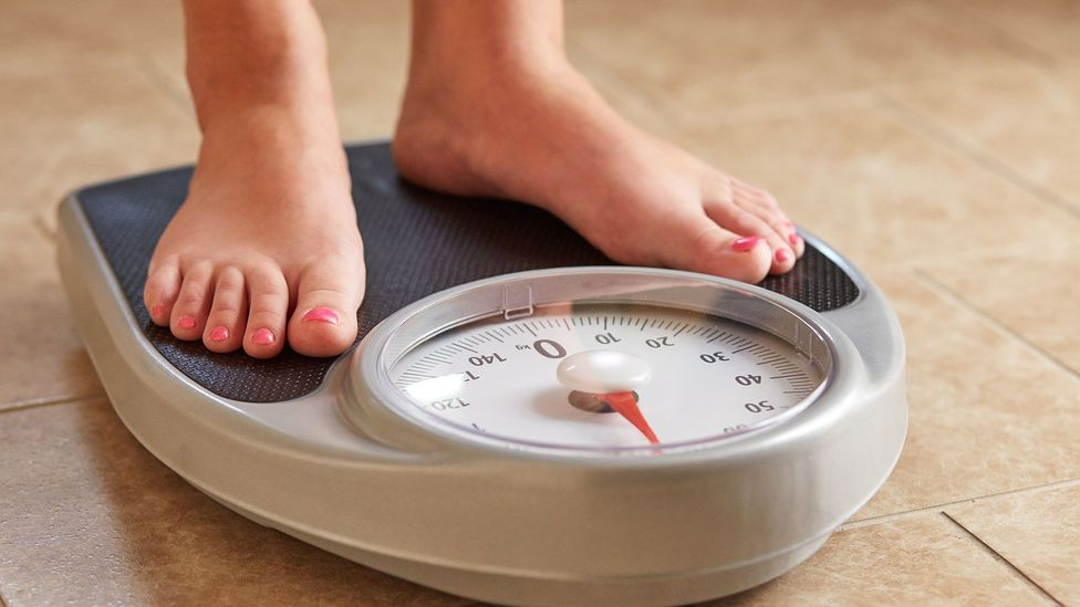 Woman on bathroom scales (Credit: Getty Images)