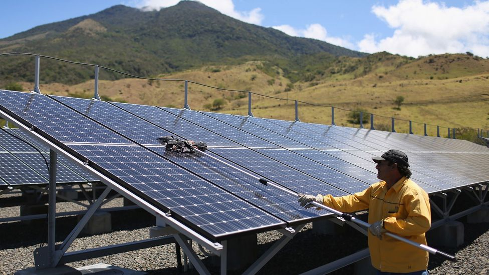 A worker cleans solar panels in Costa Rica  in 2015; last year, 98% of the country's electricity came from renewable energy sources (Credit: Getty)