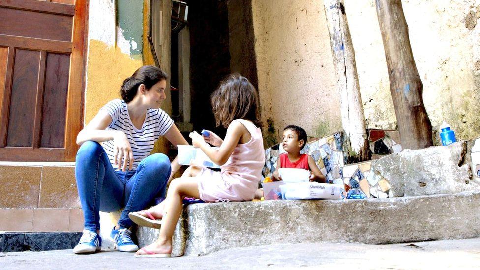 Elisa Mansur sits with children