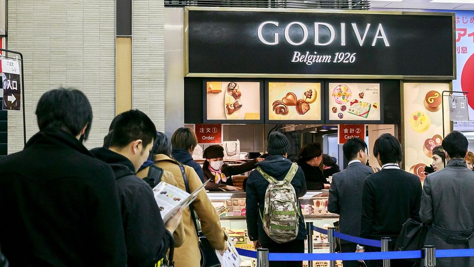 Men queueing outside a Godiva shop in Tokyo in 2016 to purchase White Day gifts for the women who gave them chocolates on Valentine's Day (Credit: Alamy Stock Photo)