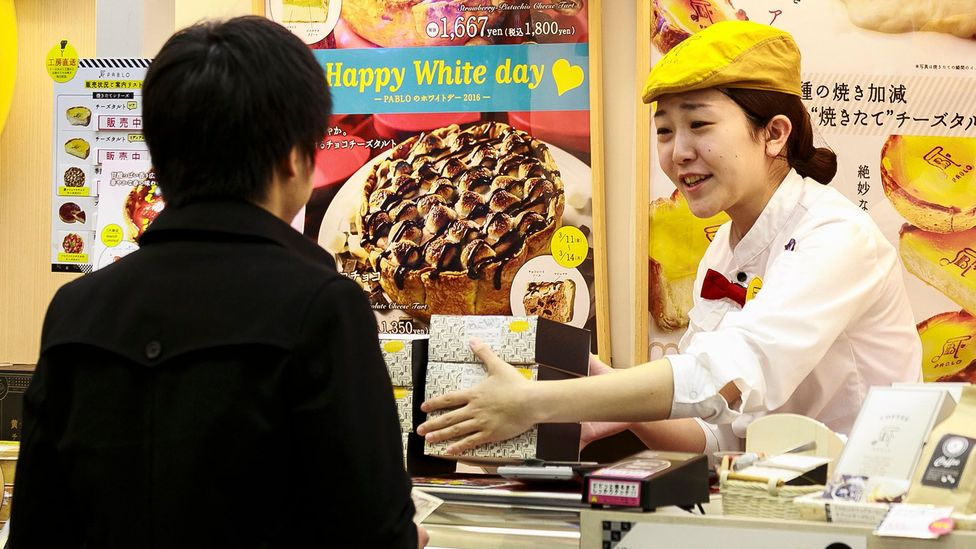 A clerk assisting a man with a White Day purchase. Spending for both Valentine's Day in February and White Day in March in Japan were down last year (Credit: Alamy Stock Photo)