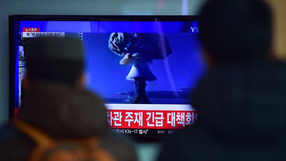 Passers-by watch the broadcast of a nuclear weapon test in North Korea (Credit: Getty Images)