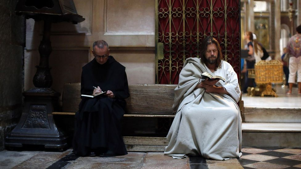 A pilgrim reads the Bible at Jerusalem's Church of the Holy Sepulchre (Credit: Getty)