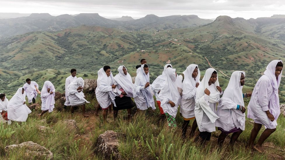Followers of the Nazareth Baptist Church climb the Nhlangakazi Holy Mountain. Religious beliefs and rituals help to unite groups of individuals (Credit: Getty)