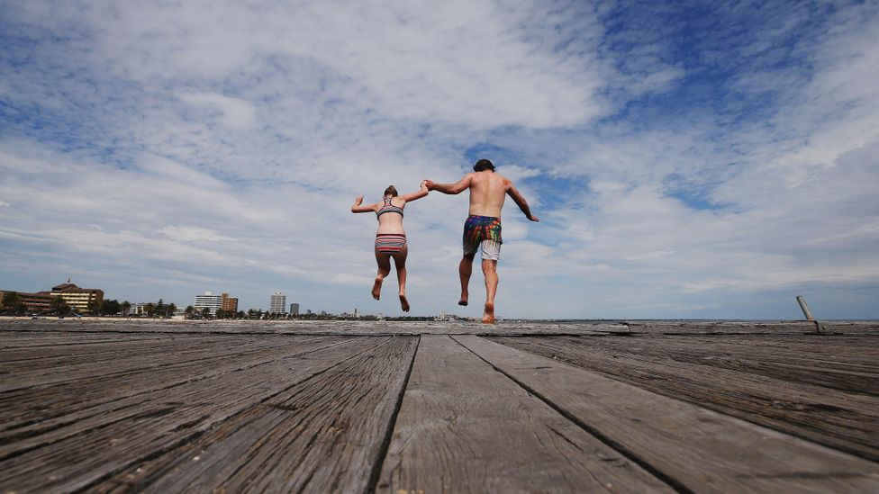 Father and daughter jump off the pier at South Melbourne Beach (Credit: Getty)