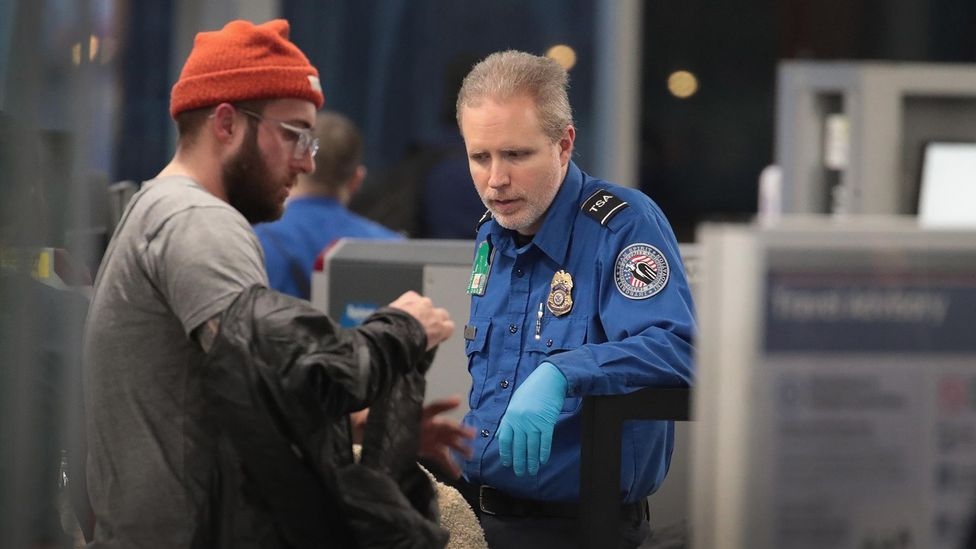 A Transportation Security Administration (TSA) worker screens passengers and airport employees at Chicago's O'Hare International Airport (Credit: Getty Images)